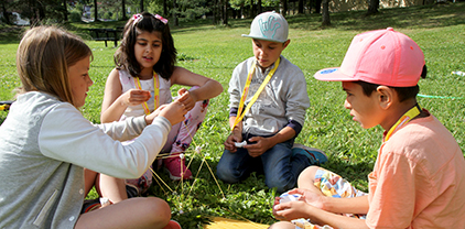 Barn på kurs som bygger tårn med spaghetti ute i gresset